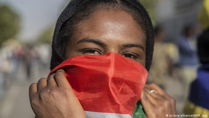 A Sudanese demonstrator holds a flag over her face