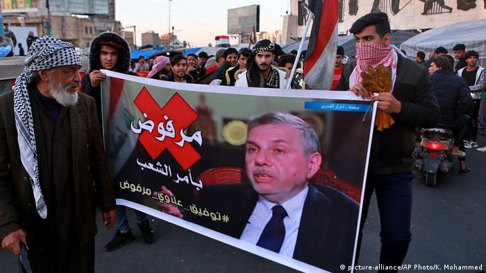 Protesters chant slogans while holding a poster of newly appointed Prime Minister Mohammed Allawi
