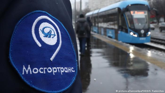 Человек в куртке с логотипом Мосгортранса и трамвай