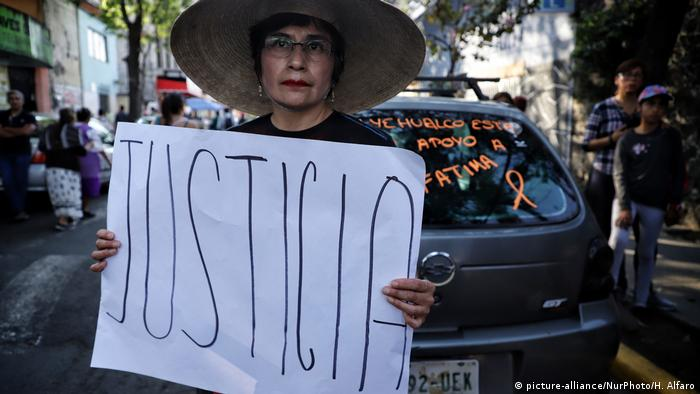 A protester holds a sign that reads justice in Spanish