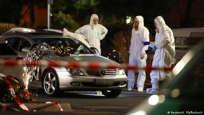 Forensic investigators behind a cordon