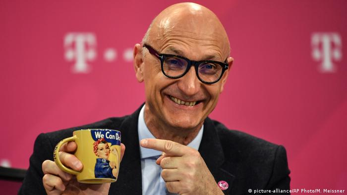 CEO of Deutsche Telekom Timotheus Hoettges holds a coffee mug reading we can do it at the annual press conference at the headquarters in Bonn, Germany, Wednesday, Feb. 19, 2020.