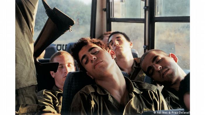 Young soldiers sleeping in a bus, one with his head on another's shoulder (Adi Nes & Praz-Delavallade Paris)