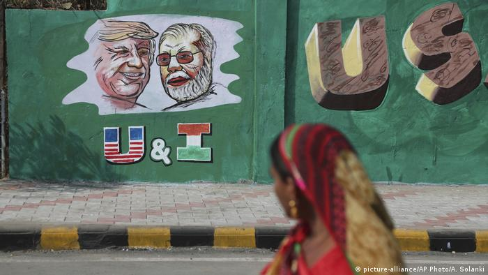 An Indian woman looks at a wall painted with portraits of U.S. President Donald Trump and Indian Prime Minister Narendra Modi ahead of Trump's visit, in Ahmadabad, India, Tuesday, Feb. 18, 2020