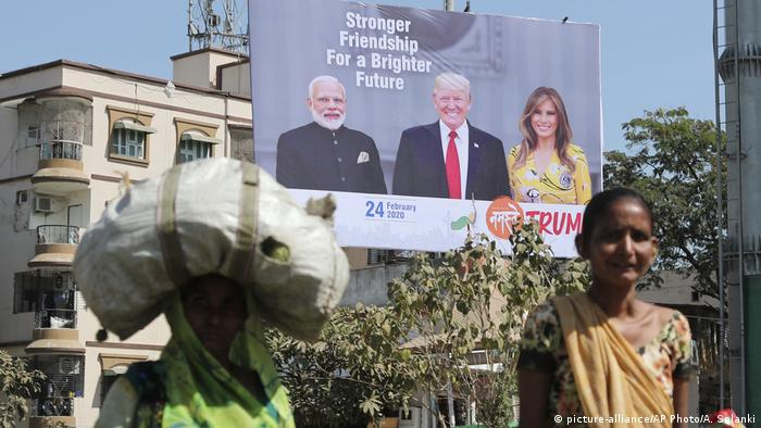 Locals stand in front of a Trump-Modi billboard, one man carries large sack on his back (picture-alliance/AP Photo/A. Solanki)
