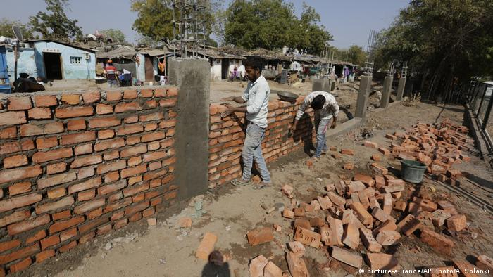Bricklayers build a wall in front of slum (picture-alliance/AP Photo/A. Solanki)