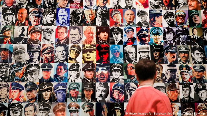 Man stands before a collage of faces of military men (Getty Images for Barbican Art Gallery/Tristan Fewings)