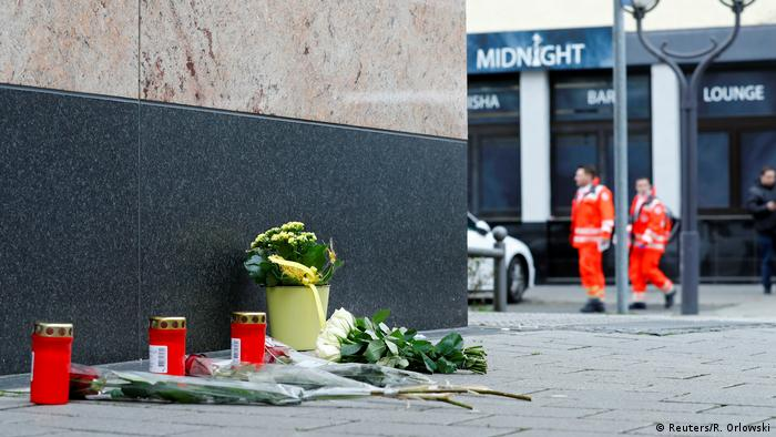 Flowers and candles are placed near the Midnight Shisha bar after a shooting in Hanau