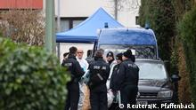 Police officers are seen outside the house of the suspected gunman