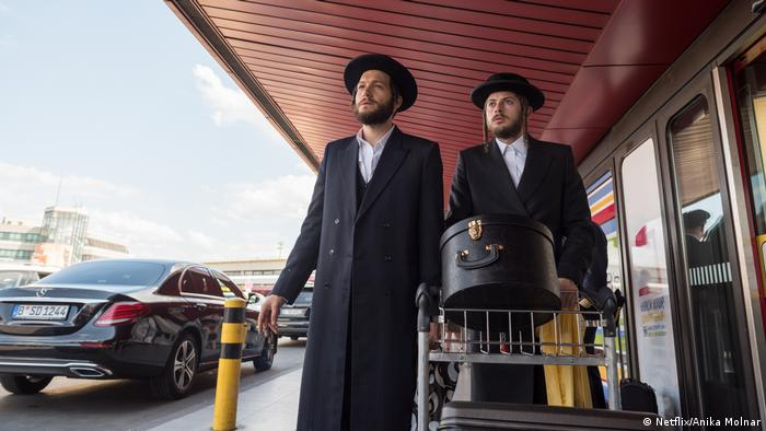 Filmstill aus der Netflix-Serie Unorthodox - zwei Männer in langen Mänteln schieben einen Trolley mit Koffern