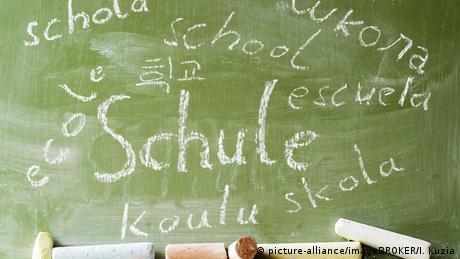 Das Wort Schule in mehreren Sprachen auf einer Tafel