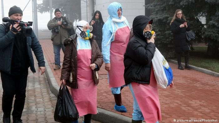 People walking with gas masks in the city of Novi Sanzhary