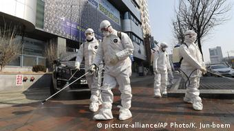 Workers in protective gear spray disinfectant outside a church in Daegu, South Korea