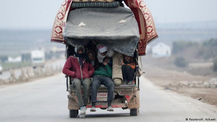 Internally displaced people, who fled from Idlib, ride on a pick up truck with their belongings in Azaz, Syria