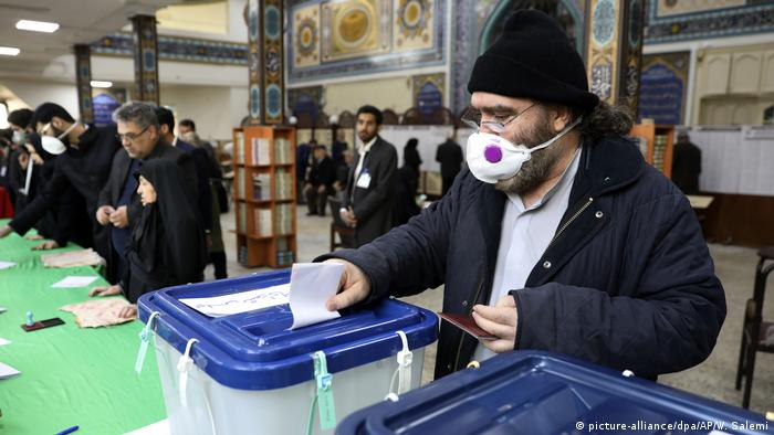 An man in Iran wears a medical face mask as he casts his vote in parliamentary elections