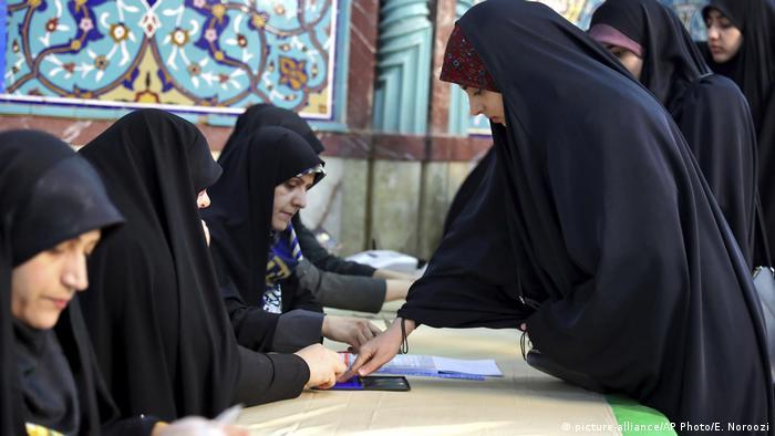 Mulheres vestidas de véu negro sentadas atendem a outra mulher de véu negro em pé, que tira impressão digital