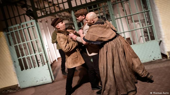 Inmates perform Fidelio in prison: three men in brown jackets and robes in an altercation in front of a door with bars