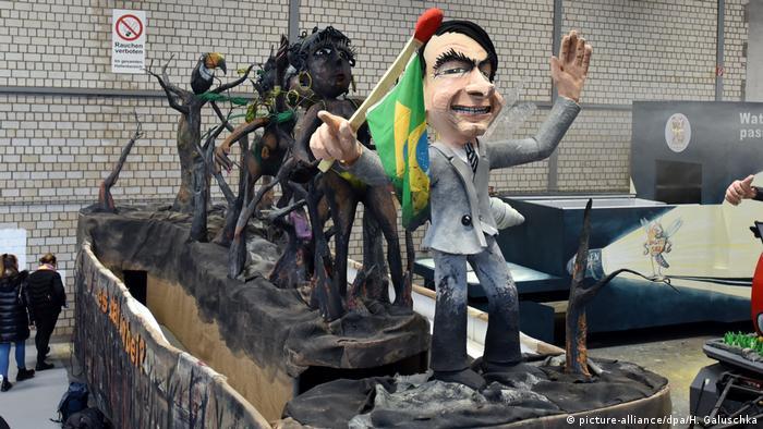 Carro alegórico com boneco do presidente Bolsonaro, árvores e passistas carbonizadas