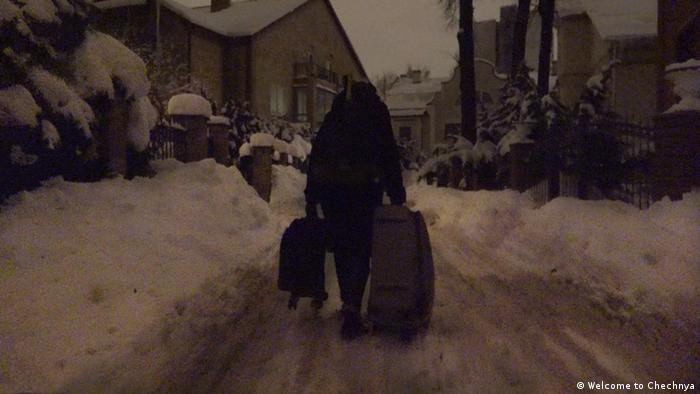 Кадр из фильма Добро пожаловать в Чечню: мужчина с чемоданами идет по улице