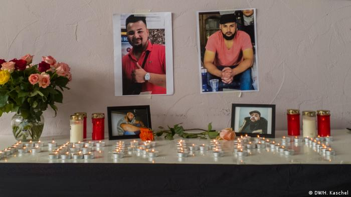 Candles, flowers, and photos on a table on display in a Kurdish cultural center in memory of Ferhat Unver, who was killed in a shooting in Hanau
