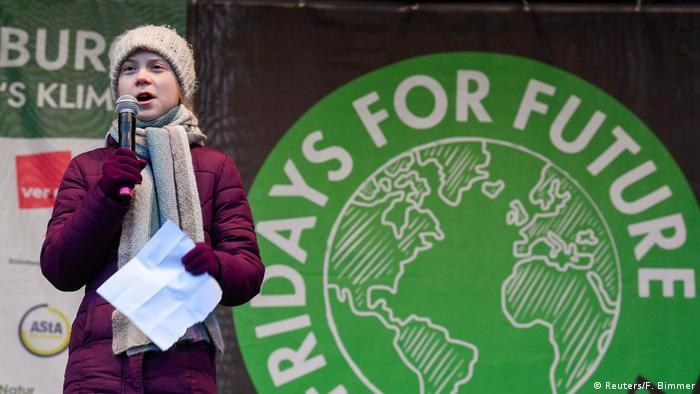 Climate activist Greta Thunberg holds a climate protest sign