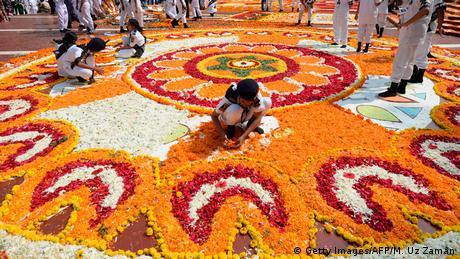 Dhaka, glavni grad Bangladeša. Na Dan maternjeg jezika djevojčice ukrašavaju spomenik hiljadama raznobojnog cvijeća. To je jedan od najvažnijih praznika u državi, jer je protestima za očuvanje bengalskog jezika počela borba za odcjepljenje Bangladeša od Pakistana. Borba je završena 1971. kada je Bangladeš postao neovisan. Dan maternjeg jezika je još uvijek jedan od najvažnijih dana u godini.