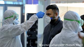 Путешествующему в защитной маске измеряют температуру в аэропорту