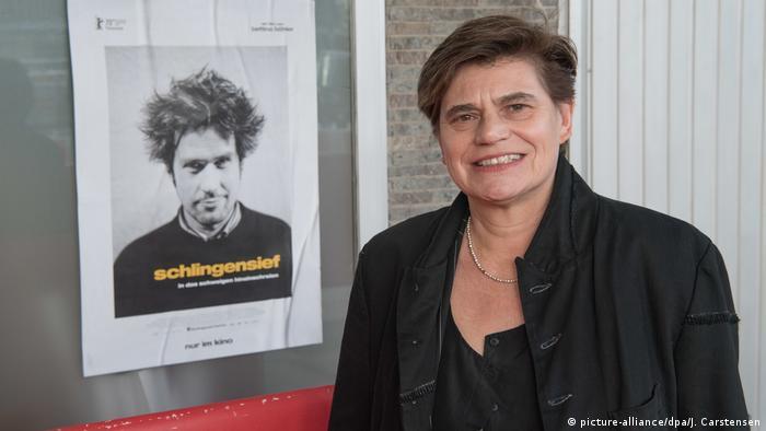 Bettina Böhler vor Plakat mit Schlingensief