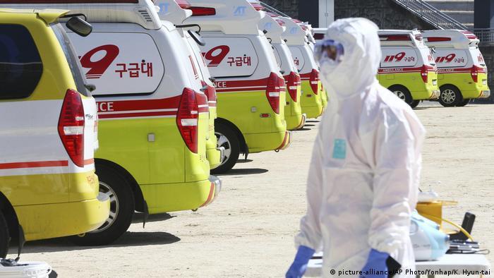 A South Korean paramedic stands behind ambulances