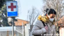 A woman wearing a face mask leaves the hospital of Codogno amid a coronavirus outbreak in northern Italy