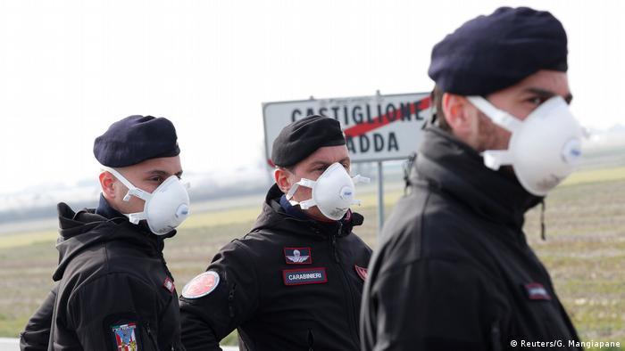 Трое итальянских полицеских в респираторных масках следят за соблюдением режима карантина на границе населенного пункта Кастильоне-д'Адда в Ломбардии.