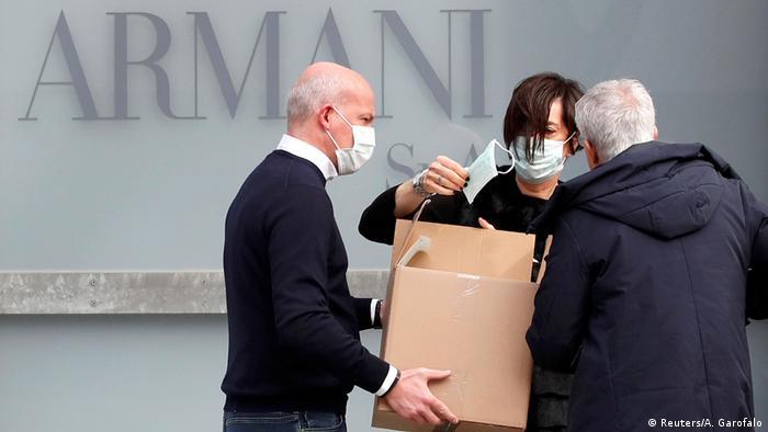 Трое мужчин в респираторных масках на фоне надписи Armani