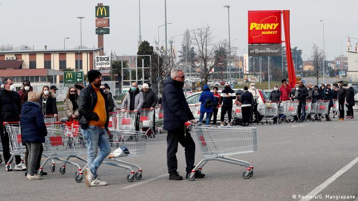 Около 30 человек выстроились в очередь у входа в супермаркет в городе Казальпустерленго. Многие итальянцы закупают продукты впрок из-за угрозы распространения коронавируса и введенного из-за нее карантина.