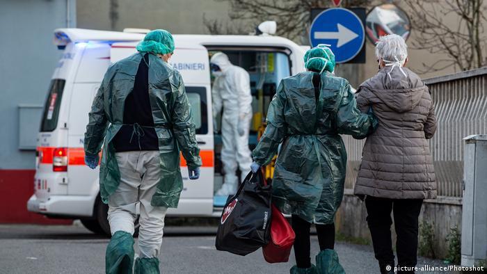 Мужчина и женщина в защитных костюмах сопровождают пожилую женщину в респираторной маске к карете скоронй помощи.