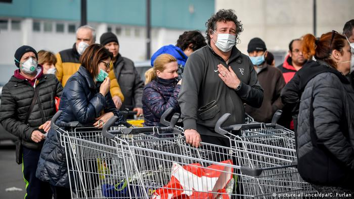 Locals in Italy facing face masks queue outside a supermarket