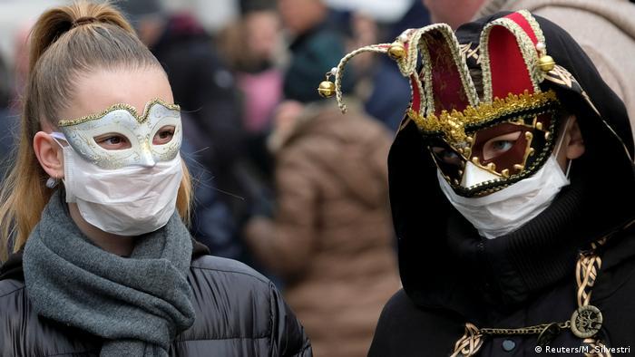 Dos personas llevan máscaras venecianas y máscaras de protección bucal.