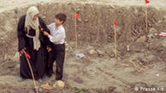 Filmstill with boy and grandmother standing at uncovered grave