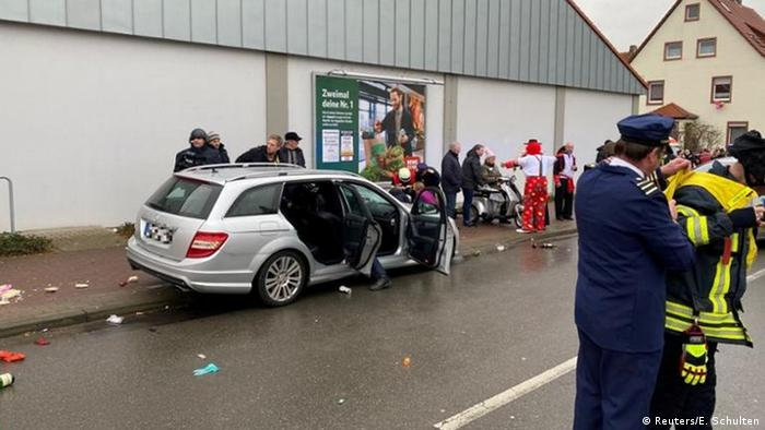 Revellers by a silver car in Volkmarsen (Reuters/E. Schulten)