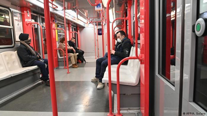 Pessoa com máscara de proteção branca em vagão de metrô