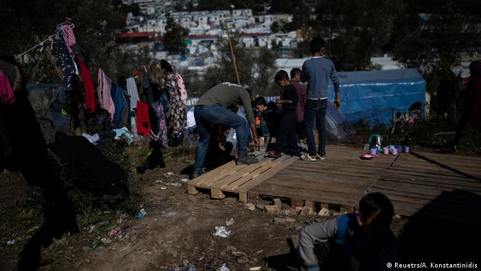 Migrants build a temporary shelter at a makeshift camp surrounding the Moria migrant camp