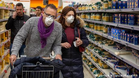 Люди в медицинских масках в продуктовом магазине в Милане