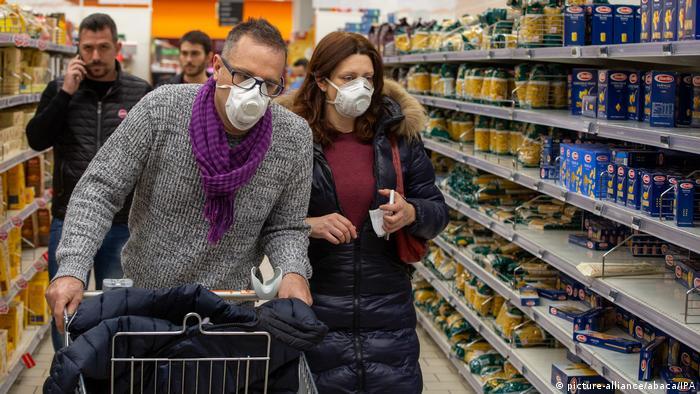 Un hombre empuja el carrito del supermercado entre los estantes, acompañado por una mujer.