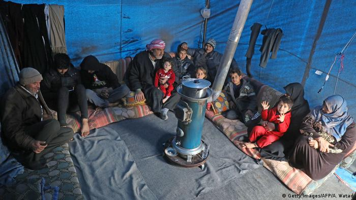 Syrian Abdel Razzak Sallat sit with his family inside a tent at an informal camp for the displaced in Kafr Lusin village