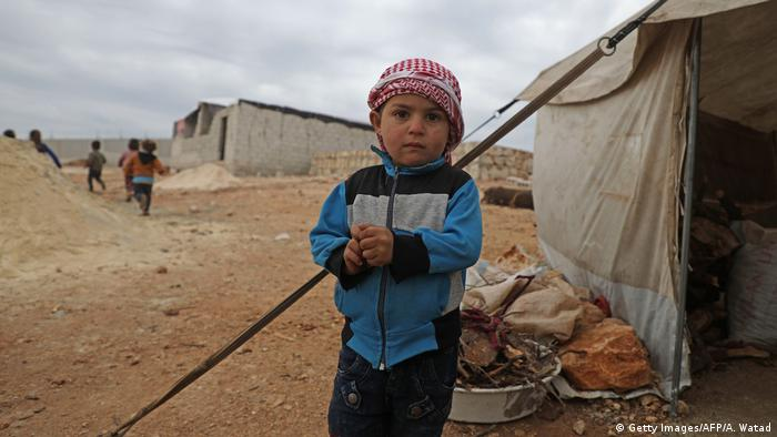 A Syrian boy stands outside a tent at an informal camp in Kafr Lusin village