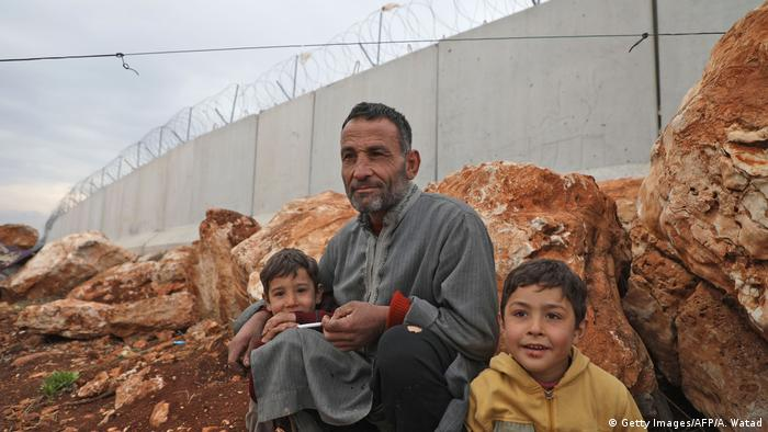 man sits with children by the Turkish border wall at an informal camp in Kafr Lusin village