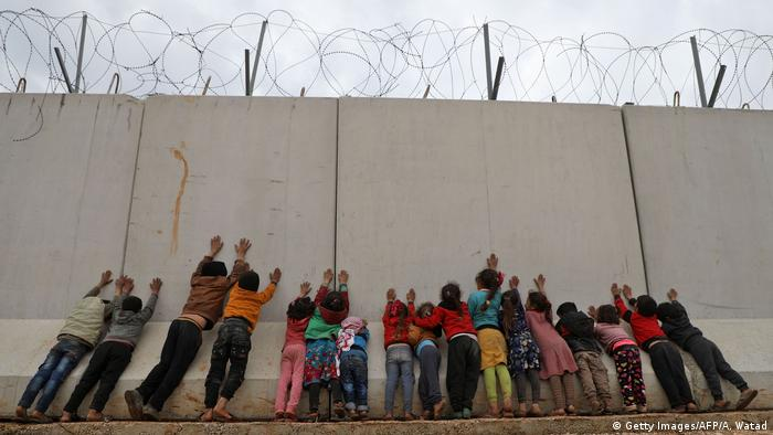 Displaced Syrian children stand by the Turkish border wall at an informal camp in Kafr Lusin village