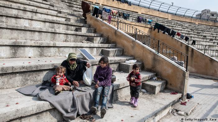 Seorang pengungsi Suriah bersama anak-anaknya duduk di tribun stadion yang diubah menjadi tempat penampungan pengungsi.