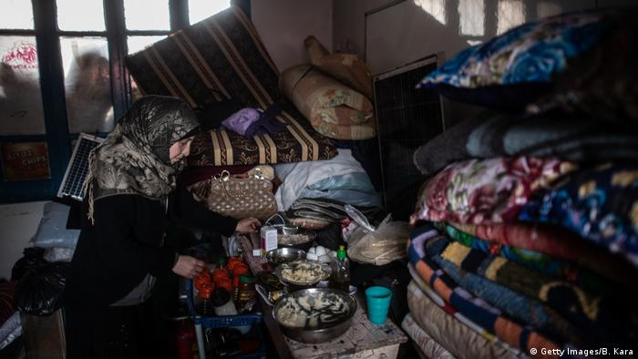 Displaced Syrian woman cooks in a classroom of a primary school turned into a makeshift refugee shelter