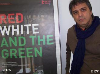 نادر داوودی در کنار پوستر مستند «سرخ، سفید و سبز»
