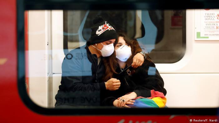 Casal sentado abraçado, ambos com máscara de respiração, visto pela janela de um vagão de trem